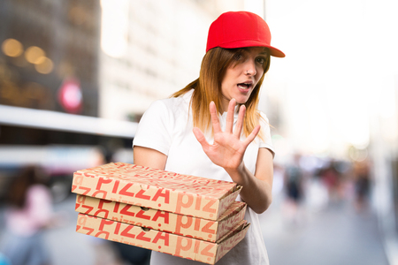 terrified woman: Frightened pizza delivery woman on unfocused background