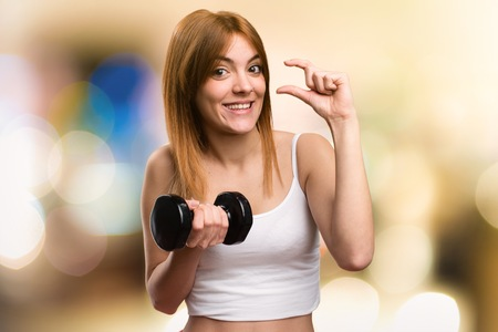 Beautiful sport woman with dumbbells making tiny sign on unfocused background