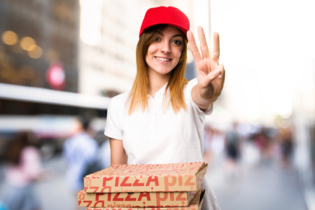 Pizza delivery woman counting three on unfocused background