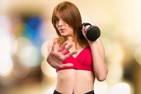 disgusted: Beautiful sport woman with dumbbells making stop sign on unfocused background Stock Photo