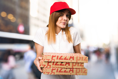 Pizza delivery woman making unimportant gesture on unfocused background