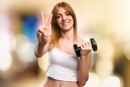 Beautiful sport woman with dumbbells counting two on unfocused background