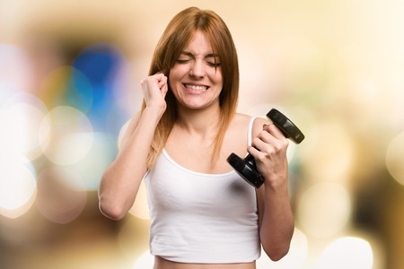Beautiful sport woman with dumbbells covering her ears on unfocused background