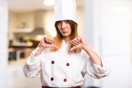 Beautiful chef woman making bad signal in the kitchen
