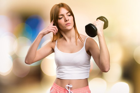 Beautiful sport woman with dumbbells making crazy gesture on unfocused background