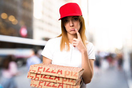 Sad pizza delivery woman on unfocused background Stock Photo