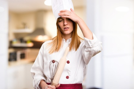 Frustrated beautiful chef woman in the kitchen Stock Photo