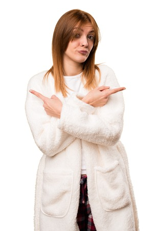 Young woman in dressing gown pointing to the laterals having doubts