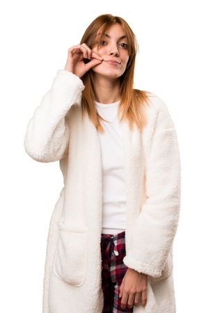 Young woman in dressing gown making silence gesture