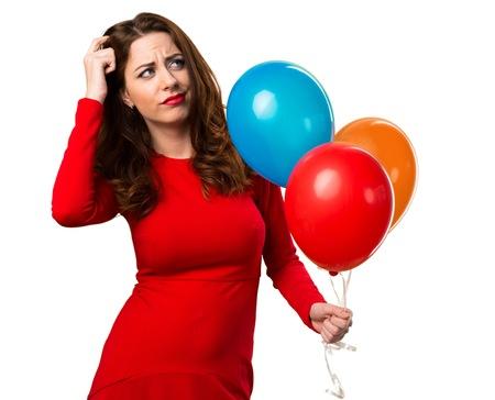 Hermosa joven sosteniendo globos y tener dudas