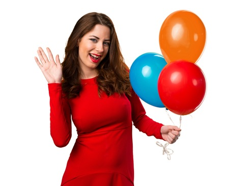 Beautiful young girl holding balloons and saluting