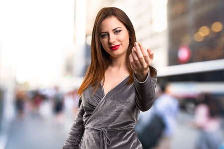 Beautiful young girl doing coming gesture on unfocused background