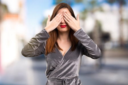 Beautiful young girl covering her eyes on unfocused background Stock Photo