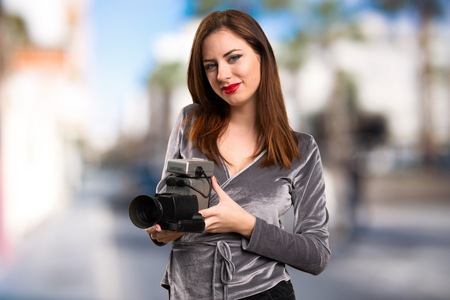 filmmaker: Beautiful young girl filming on unfocused background