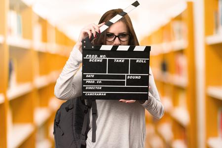 Femme étudiante tenant un clap dans une bibliothèque Banque d'images - 79635663