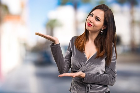 Beautiful young girl presenting something on unfocused background Stock Photo