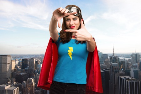 super woman: Pretty superhero girl focusing with her fingers with the city in the background