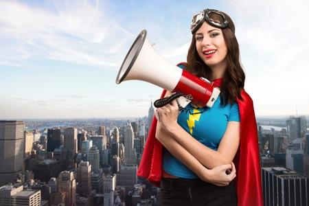 Mooi superheromeisje die door megafoon met de stad op de achtergrond schreeuwen Stockfoto