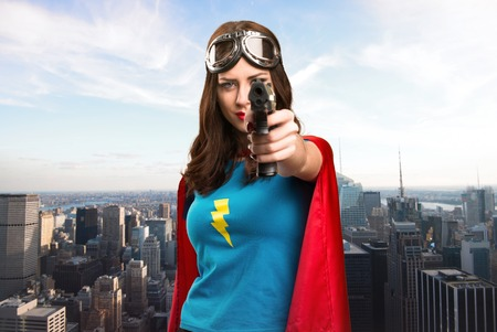 Pretty superhero girl holding a pistol with the city in the background
