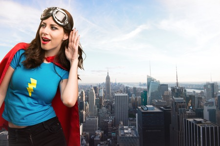 super woman: Pretty superhero girl listening something with the city in the background