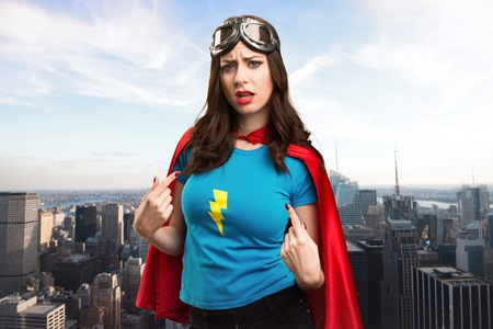 Pretty superhero girl making surprise gesture with the city in the background