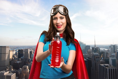 super woman: Pretty superhero girl drinking water with the city in the background