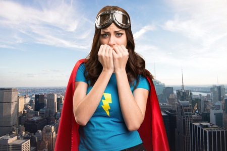super woman: Frightened  pretty superhero girl with the city in the background