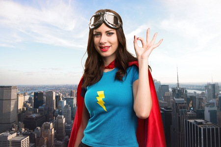alright: Pretty superhero girl making OK sign with the city in the background