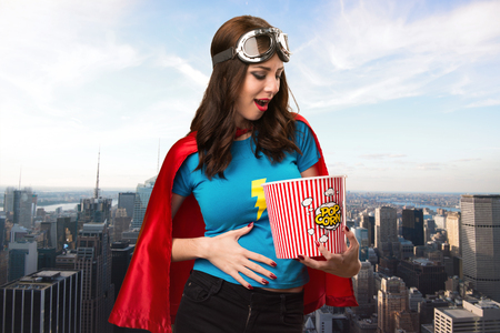 super woman: Pretty superhero girl eating popcorns with the city in the background