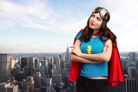 super woman: Pretty superhero girl looking up with the city in the background