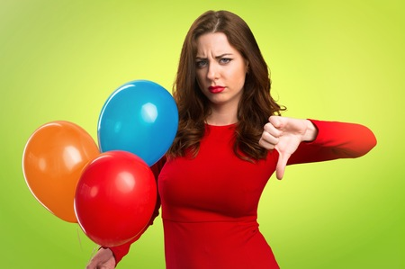 Beautiful young girl holding balloons and making bad signal on colorful background