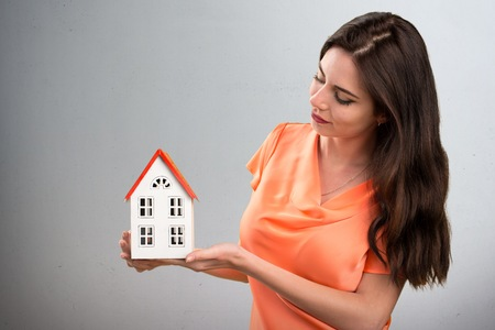 icone: Beautiful young girl holding a little house on grey background