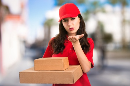 Young delivery woman sending a kiss on unfocused background