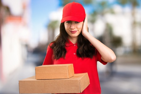 headaches: Delivery woman covering her ears on unfocused background Stock Photo