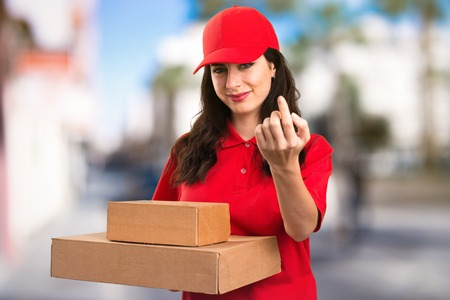 Young delivery woman doing coming gesture on unfocused background