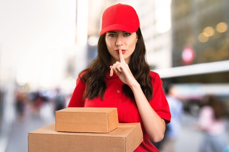Delivery woman making silence gesture on unfocused background