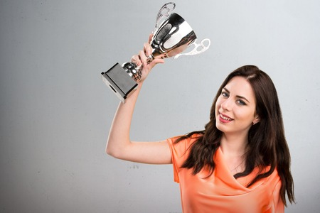 Beautiful young girl holding a trophy on grey background Stock Photo