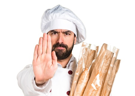Young baker holding some bread and making stop sign Stock Photo