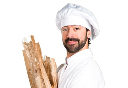 Happy young baker holding some bread Imagens