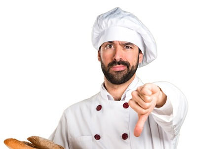 disapprove: Young baker holding some bread and making bad signal Stock Photo
