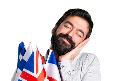 bilingual: Handsome man with beard holding many flags and making sleep gesture Stock Photo