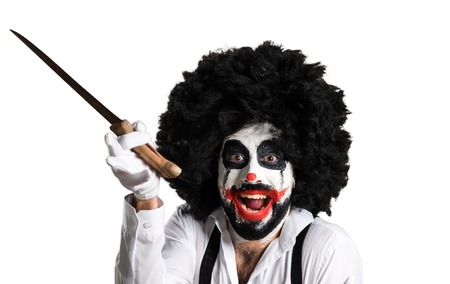 Killer clown with knife making surprise gesture