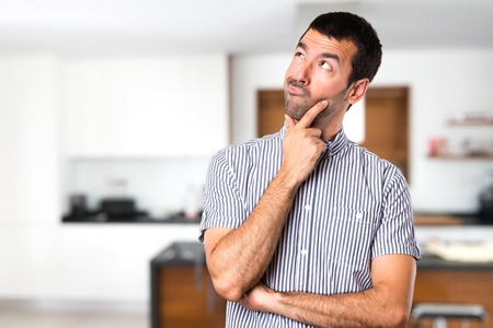Handsome man thinking inside house