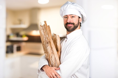 Happy young baker holding some bread in the kitchen Imagens