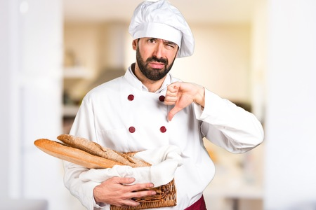 Young baker holding some bread and making bad signal in the kitchen Stock Photo