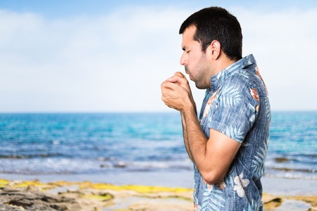 Handsome man with flower shirt coughing a lot at the beach