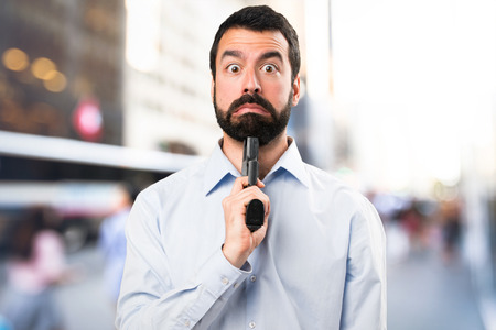 Handsome man with beard cometing suicide on unfocused background