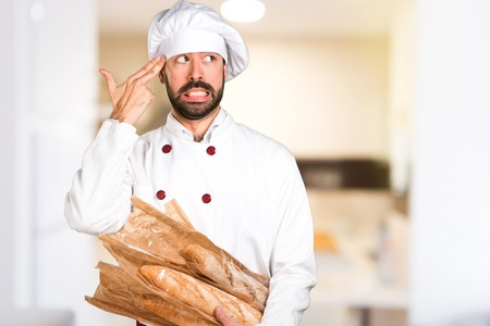 Young baker holding some bread and making suicide gesture in the kitchen