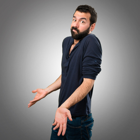 Handsome man with beard making unimportant gesture on grey background