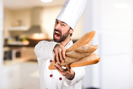 Frustrated young baker holding some bread in the kitchen